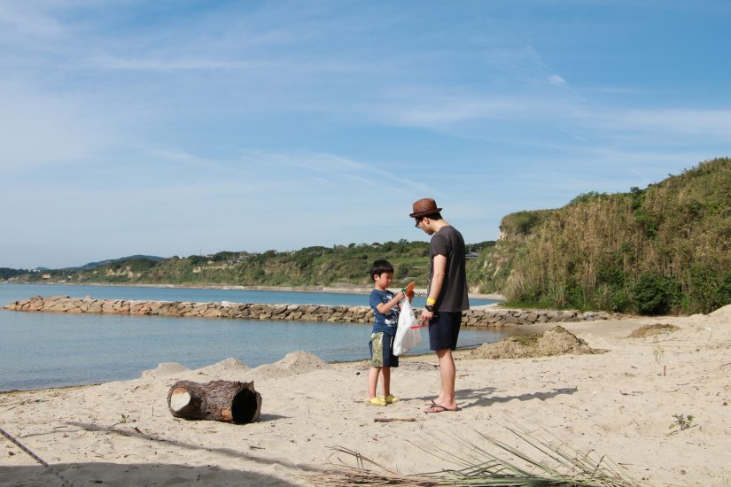 Parents and children are picking up trash at the beach as volunteering help